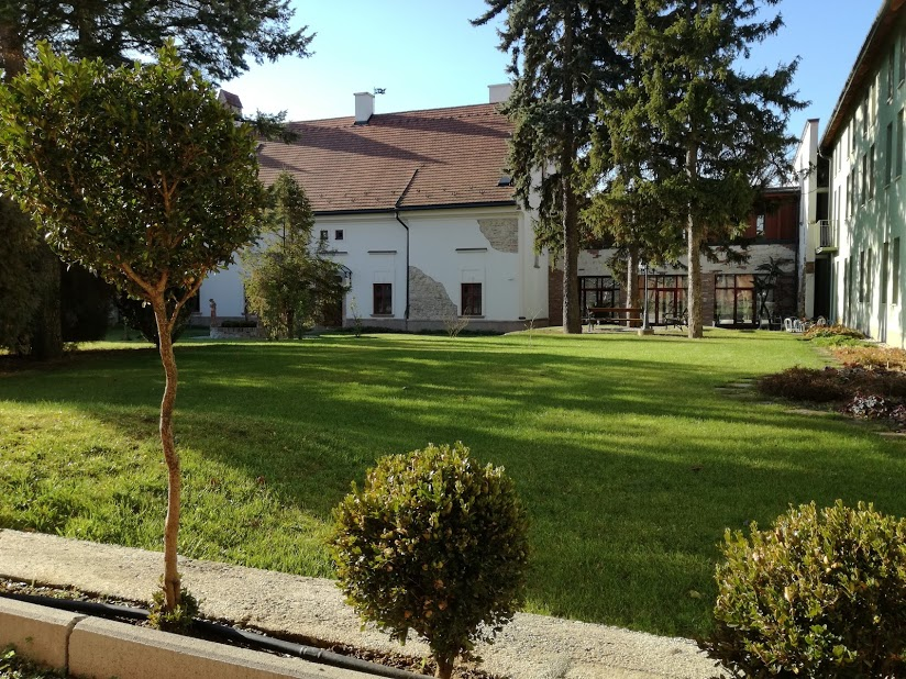 Kastélykert a kastély épülettel és a reggeliző folyosóval a háttérben